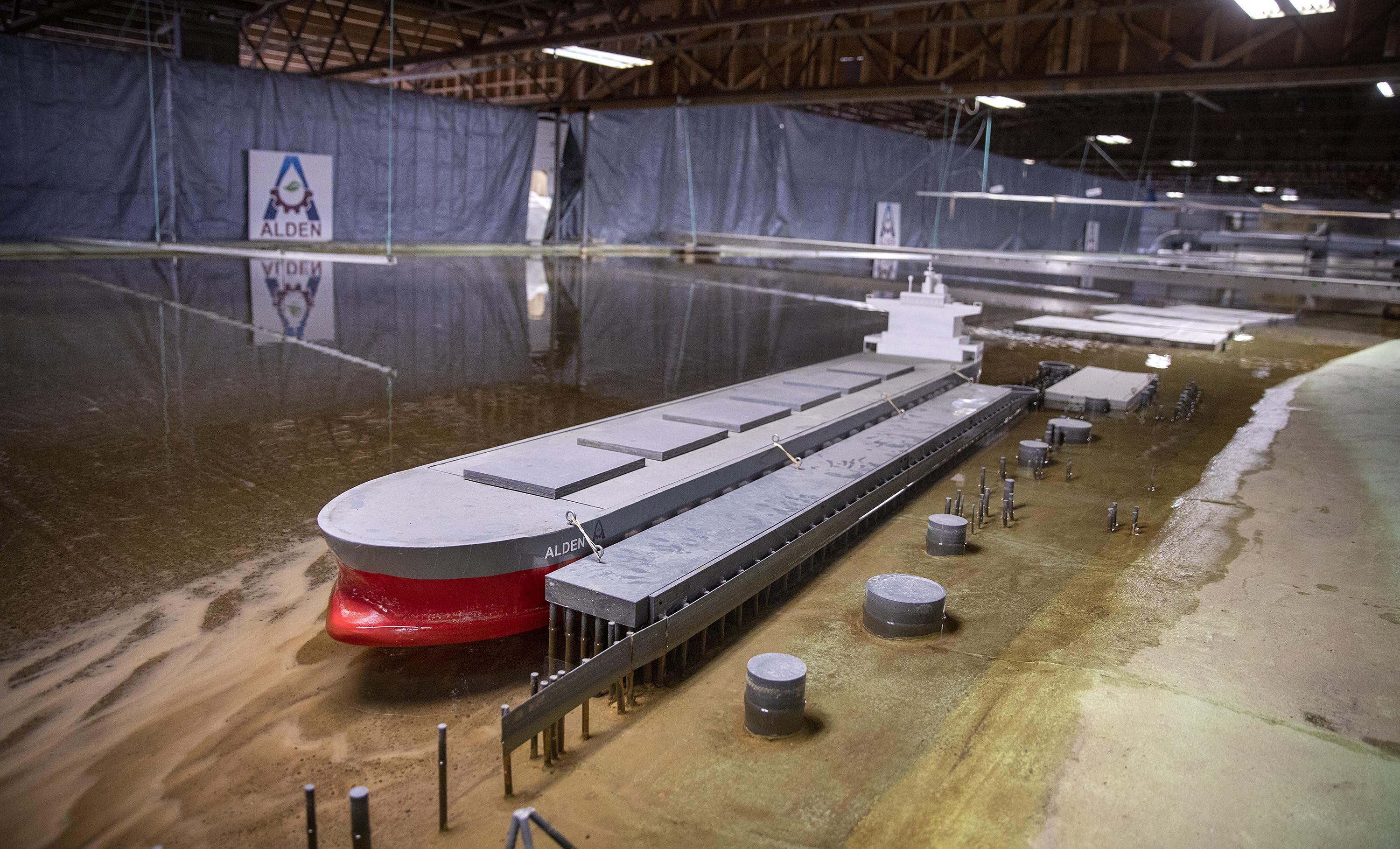 A cargo vessel lies docked on the banks of Alden's 1:65 scale model of a section of the Mississippi River. (Robin Lubbock/WBUR)