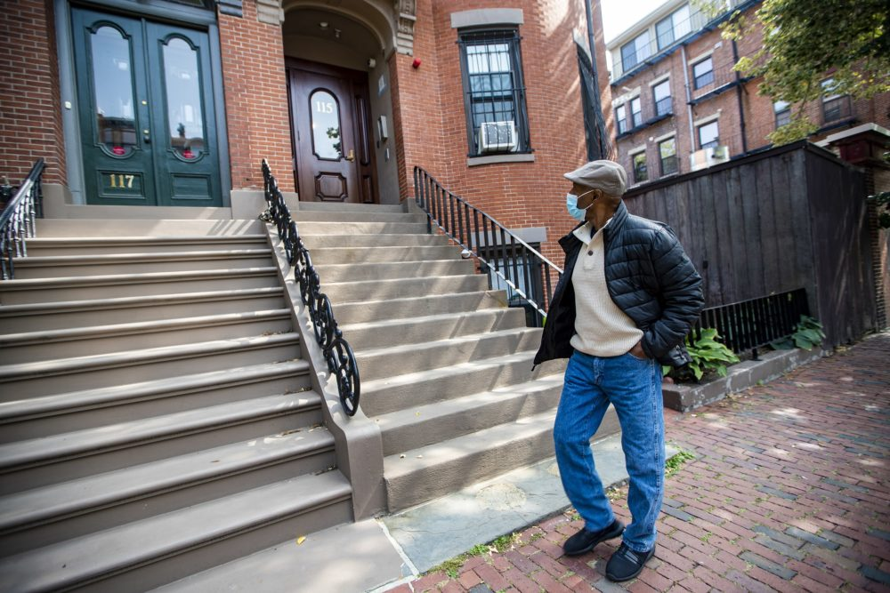 Charles Clark, of the Tenants' Development Corporation, walks past a South End brownstone, one of the affordable properties managed by the corporation. (Jesse Costa/WBUR)