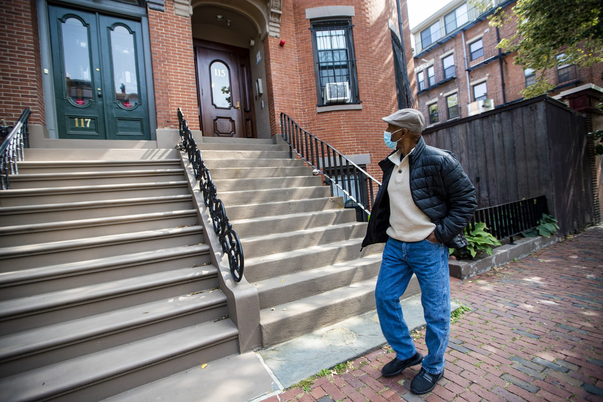 Charles Clark, of Tenants' Development Corp., walks past an apartment in the South End, one of the affordable housing properties managed by the nonprofit. (Jesse Costa/WBUR)