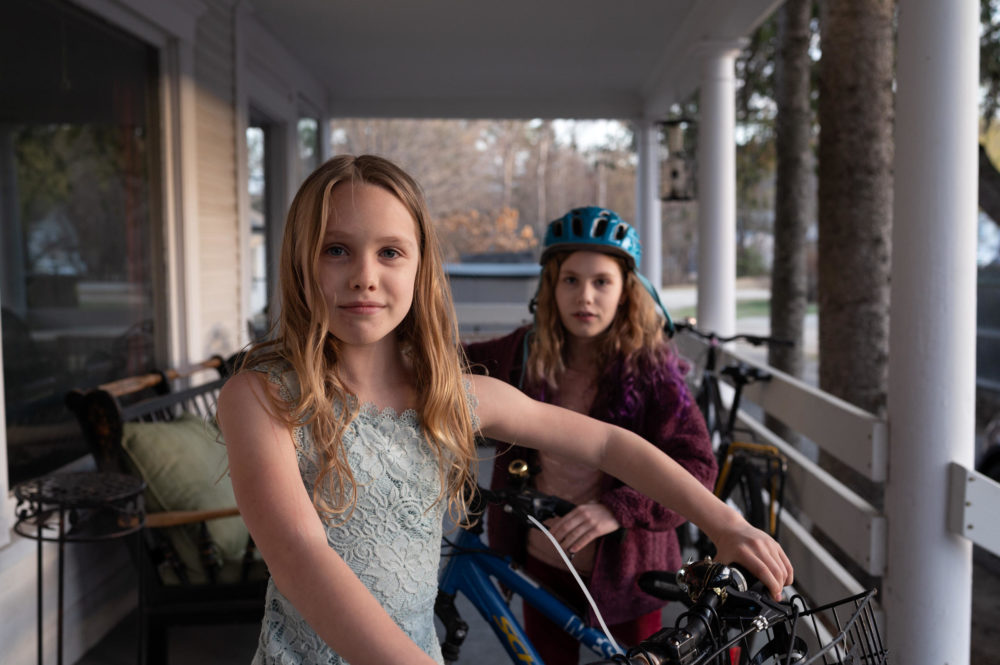 Azalea Morgan, 9, (left) and her sister Ember Morgan, 10, (right) stand with their bikes on the porch of their home in Andover, New Hampshire. The sisters biked to New York City from Andover with their mom to raise awareness of climate change in 2019. (Ryan Caron King/Connecticut Public)