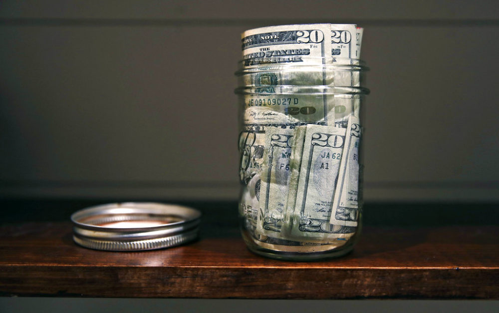 In this June 15, 2018, photo a canning jar filled with currency sits on a shelf in East Derry, N.H. (AP Photo/Charles Krupa)