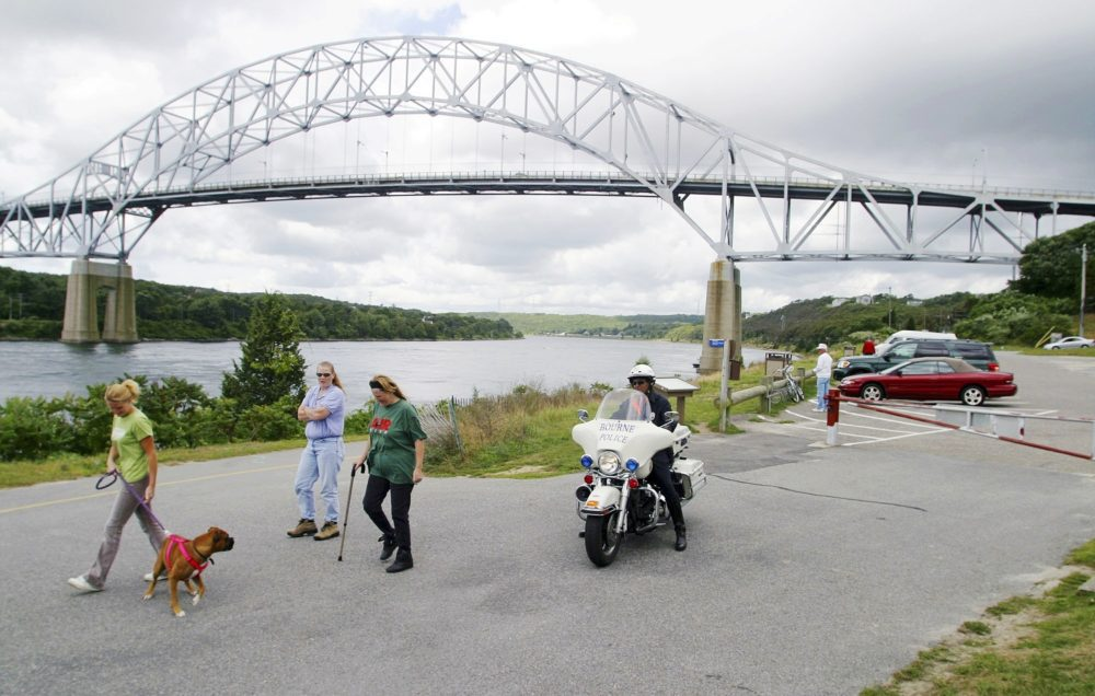 In this Sept. 9, 2003 photo, a police officer patrols as pedestrians walk along the Cape Cod Canal beneath the Sagamore bridge in Bourne, Mass. (Julia Cumes/AP)