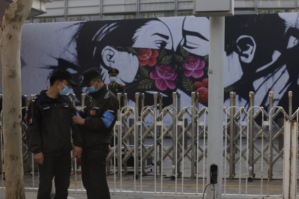 Chinese security personnel stand on duty near an art work outside the United States Embassy in Beijing on April 6, 2021. China accused the U.S. of causing humanitarian disasters through foreign military interventions in a report Friday, April 9, 2021 that was the latest broadside by Beijing amid increasingly contentious relations with the Biden administration. (Ng Han Guan/Associated Press)
