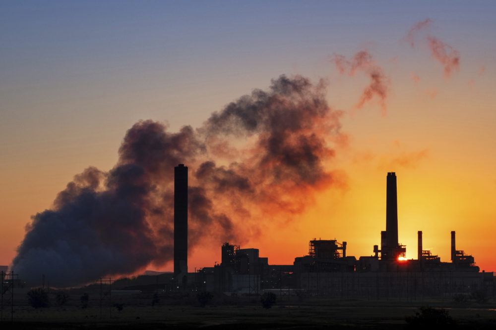The Dave Johnson coal-fired power plant is silhouetted against the morning sun in Glenrock, Wyoming, in 2018. (J. David Ake/AP/File)
