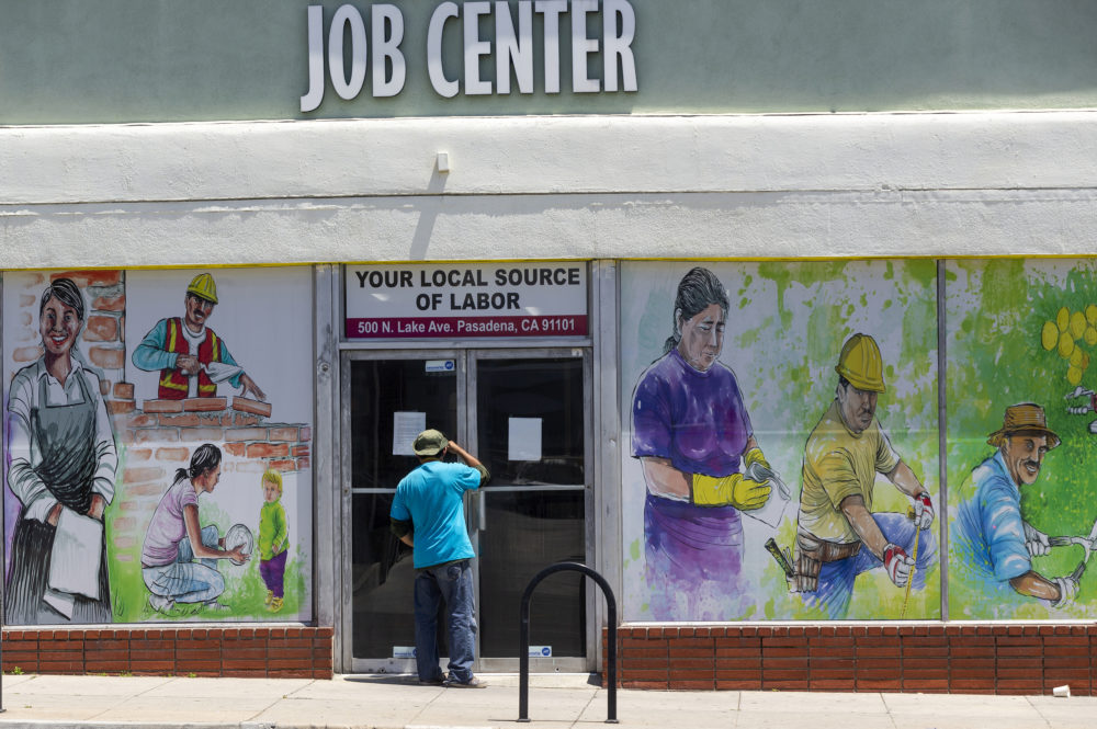 In this May 7, 2020, file photo, a person looks inside the closed doors of the Pasadena Community Job Center in Pasadena, Calif., during the coronavirus outbreak. (Damian Dovarganes/AP File)