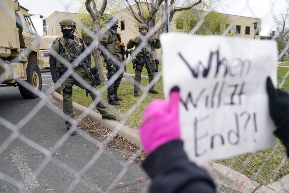 Police stand guard as demonstrators gather outside the Brooklyn Center Police Department to protest the shooting death of Daunte Wright, Tuesday, April 13, 2021, in Brooklyn Center, Minn. (John Minchillo/AP)