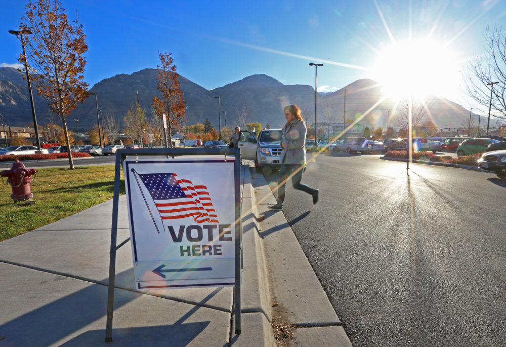 A woman walks into a polling center to vote in the midterm elections as the morning sun rises over the Utah Wasatch Mountains on November 6, 2018 in Provo, Utah. (George Frey/Getty Images)