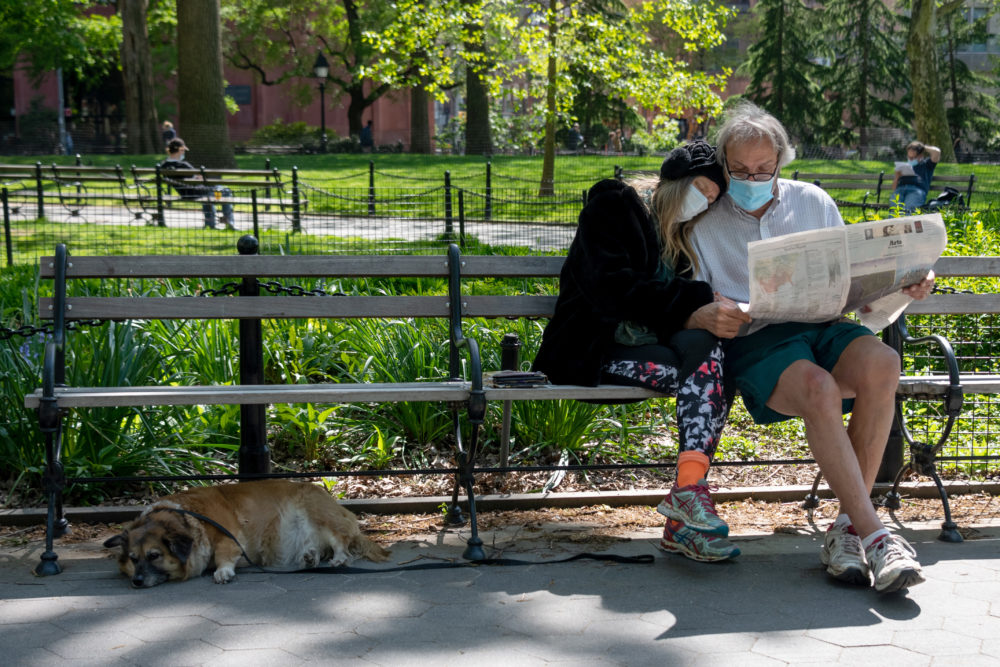A couple wearing masks sits together reading the newspaper in New York City. (Alexi Rosenfeld/Getty Images)