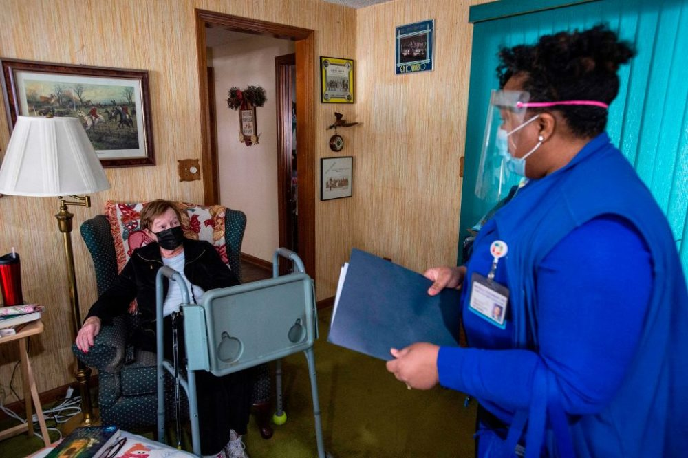 R.N Natalie O'Connor greets her first patient of the day Rita Fuller, 83, at her home and goes over a COVID-19 pre-vaccine checklist before administering it in Manchester, Connecticut on February 12, 2021. (Photo by Joseph Prezioso/AFP via Getty Images)