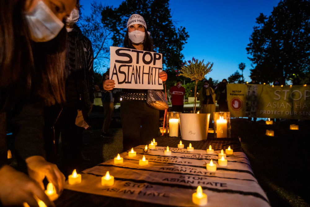 Vanessa Nguyen holds a Stop Asian Hate sign while joining community leaders during a candlelight vigil mourning the victims of the Atlanta shootings, in Garden Grove, CA, on March 23, 2021. (Allen J. Schaben / Los Angeles Times via Getty Images)