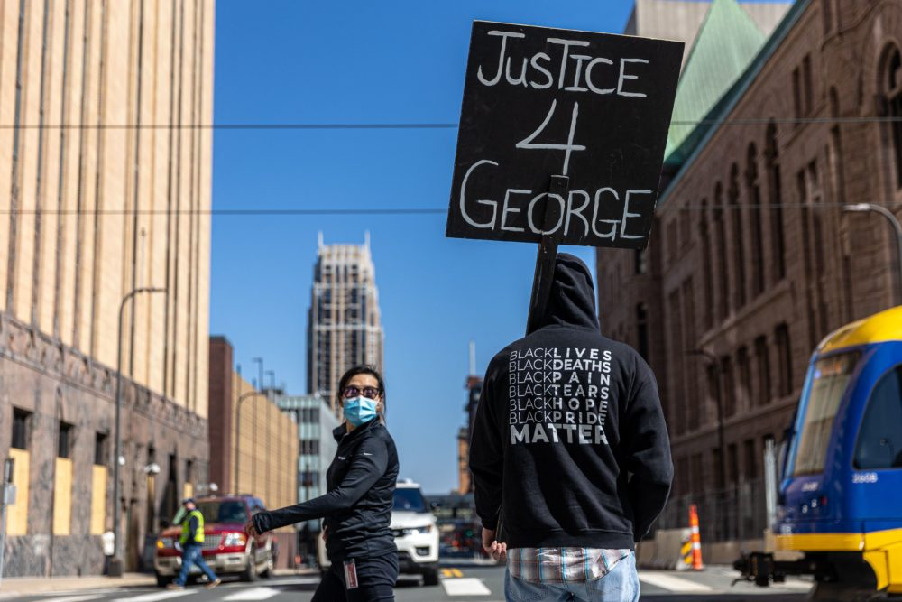 """A demonstrator hold a sign """"Justice for George"""" outside the Hennepin County Government Center during the opening statement of former Minneapolis Police officer Derek Chauvin on March 29, 2021 in Minneapolis, Minnesota. (Kerem Yucel/AFP via Getty Images)"""