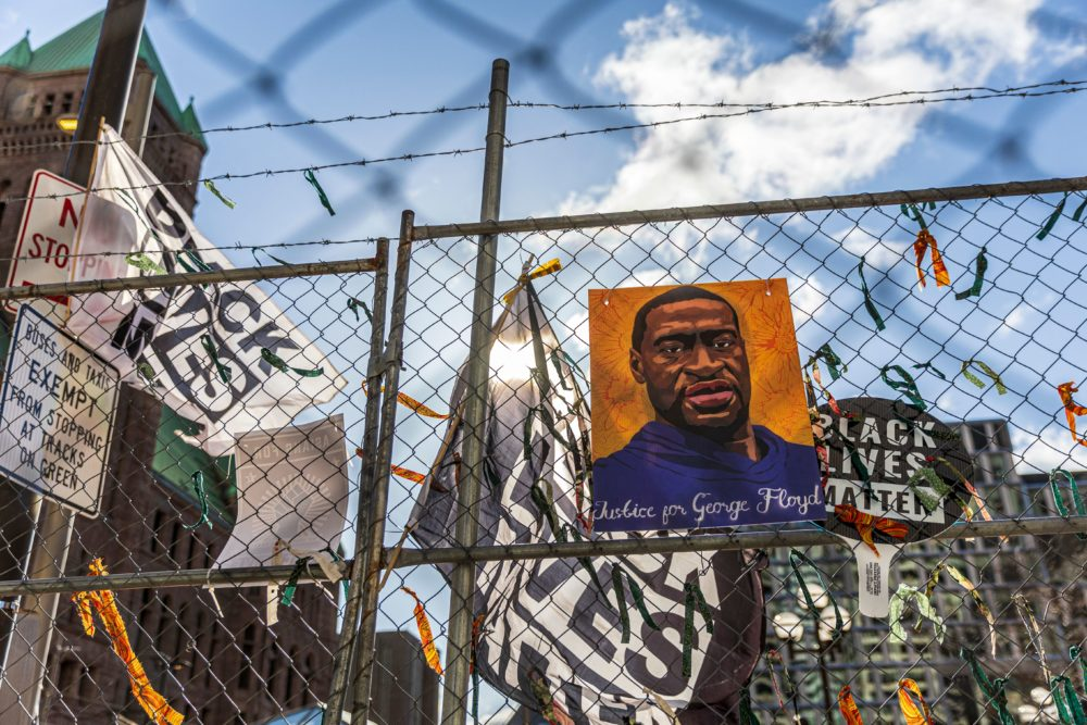 """A poster with George Floyd's picture and a sign reads that """"I Can't Breathe"""" hang from a security fence outside the Hennepin County Government Center on March 31, 2021 in Minneapolis, Minnesota. (Kerem Yucel/AFP via Getty Images)"""