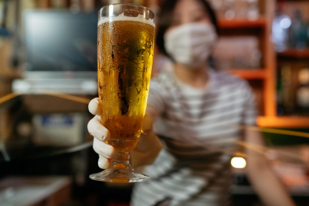 A masked bar owner serves beer during the pandemic. (Getty Images)