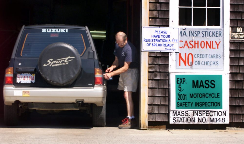 Allen Pornovish checks the gas cap during an inspection of a Suzuki Sidekick. (Wendy Maeda/The Boston Globe via Getty Images)