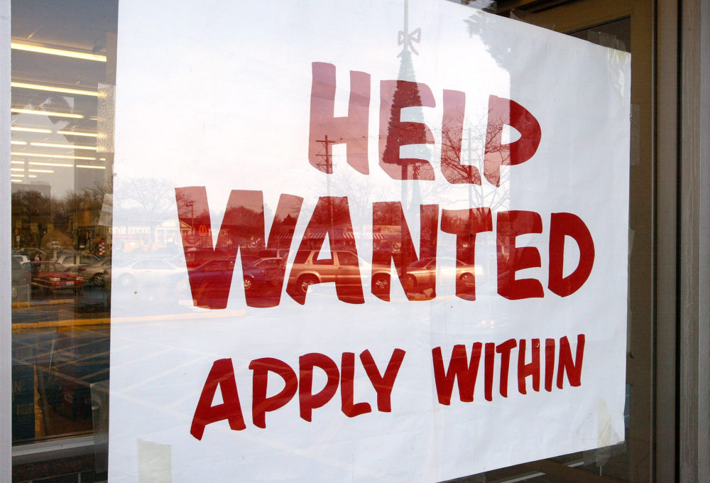"""A sign that reads """"Help Wanted Apply Within"""" is seen hanging in a window of a beverage store. (Tim Boyle/Getty Images)"""