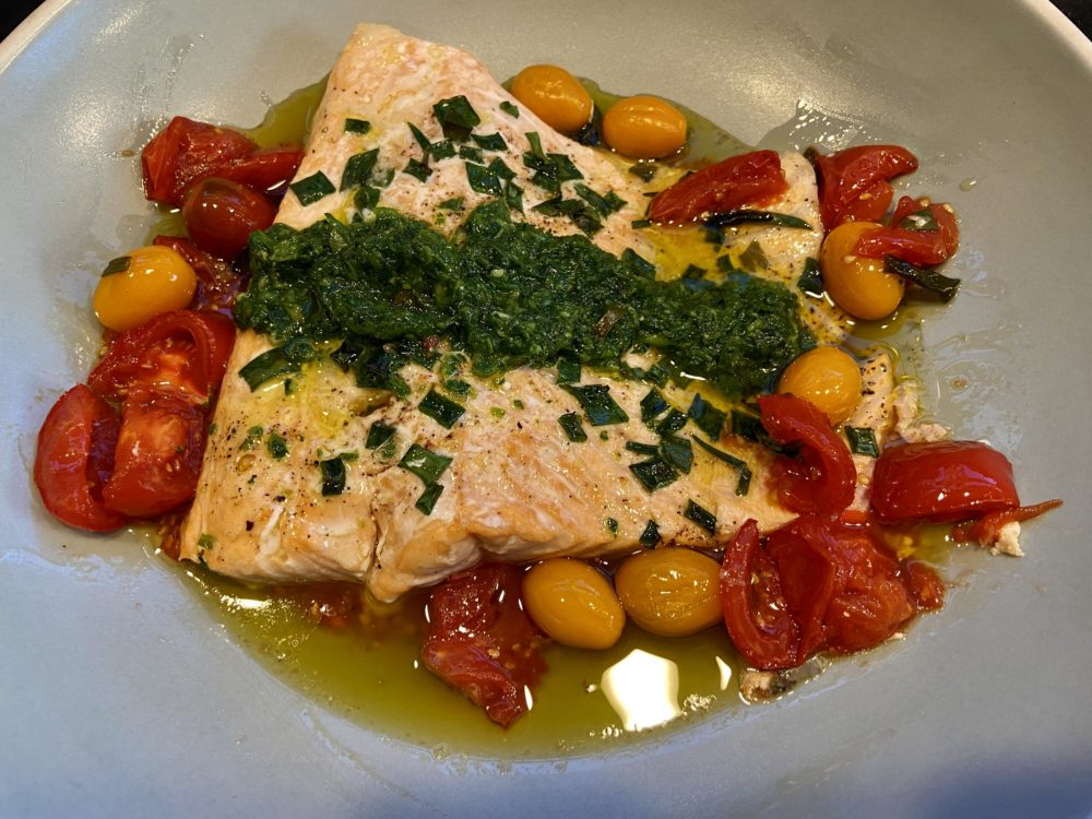 Roasted salmon with cherry tomatoes, scallions and green sauce. (Kathy Gunst)