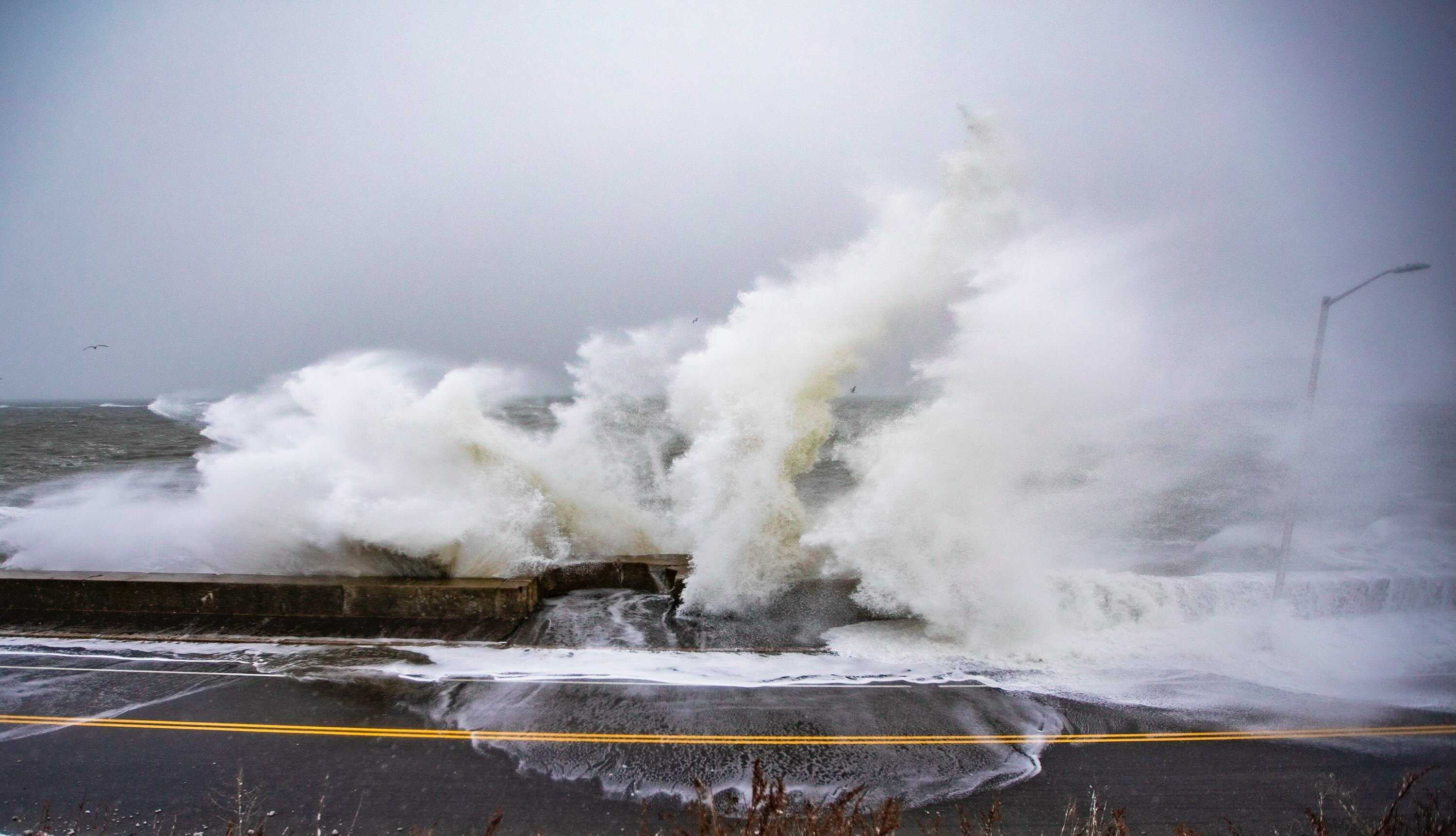 Waves crash over the seawall on Winthrop Parkway in Revere during a high tide on Dec. 17, 2020. (Jesse Costa/WBUR)
