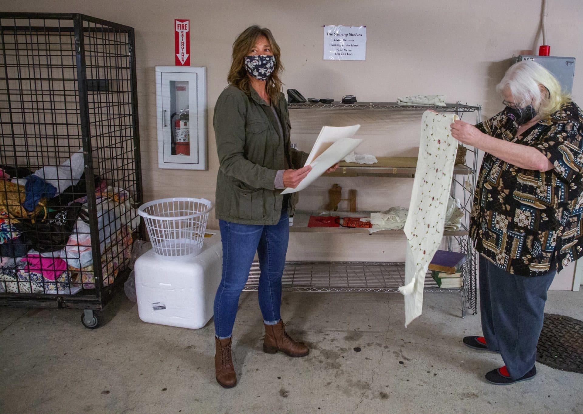 """Kim Loveall Price, izquierda, y Joyce Hansbearry, administradora de la residencia de los apartamentos, miran artículos de los """"estantes para compartir"""" en Ashwood Court.  (Mike Seigel para WBUR)"""