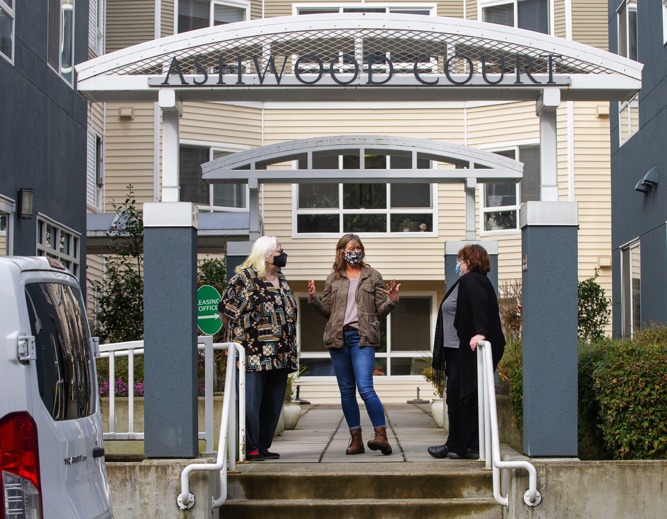 Kim Loveall Price, centro, directora de una organización sin fines de lucro que opera Ashwood Court, un complejo de viviendas para personas de bajos ingresos en Bellevue, Washington, habla con los residentes Susanne Sherman, derecha, y Joyce Hansbearry.  (Mike Seigel para WBUR)