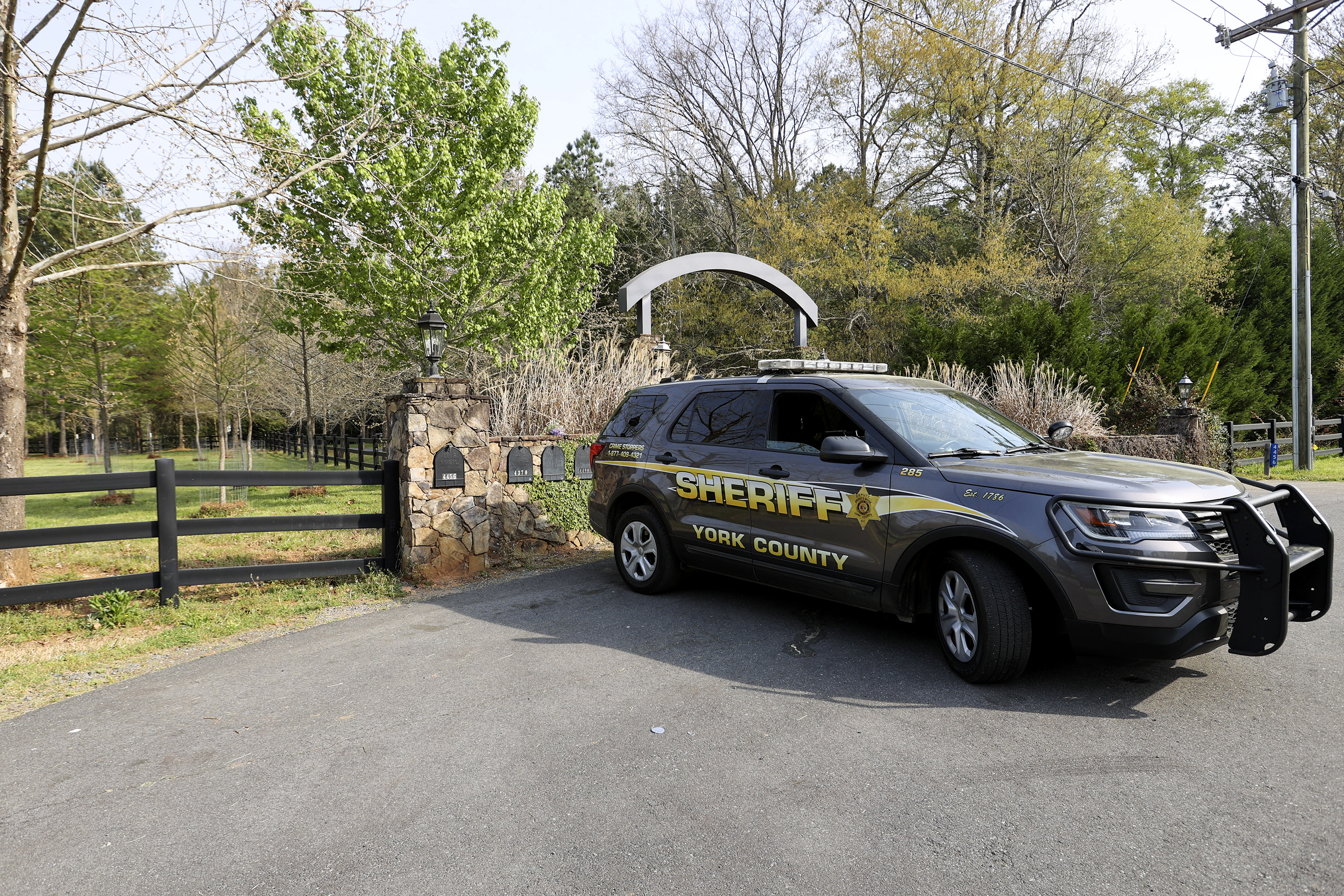 A York County sheriff's deputy is parked outside a residence where multiple people, including a prominent doctor, were fatally shot a day earlier, on April 8 in Rock Hill, S.C. (Nell Redmond/AP)