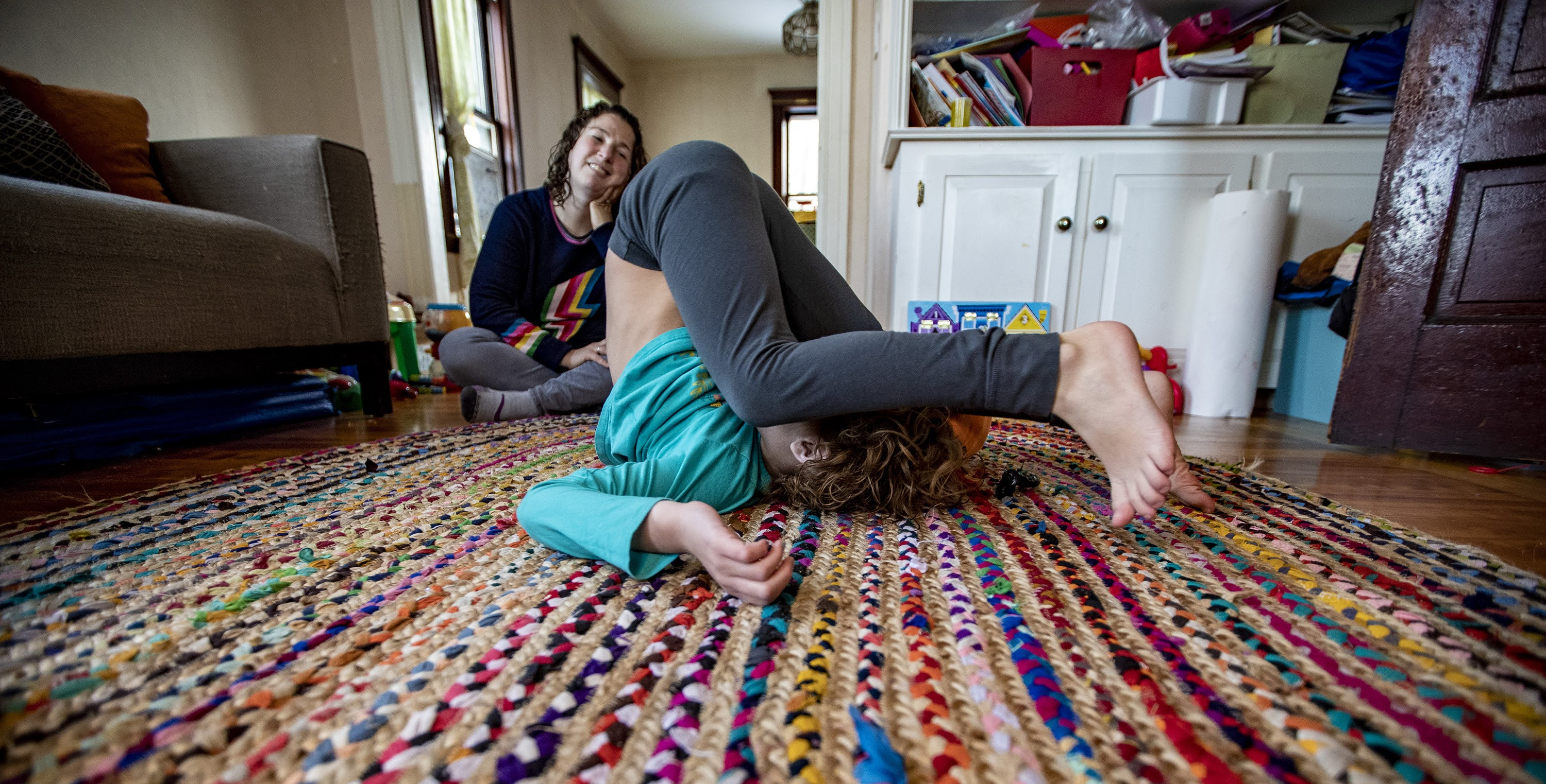 Hallel does a backwards roll in the living room as their mother watches. (Jesse Costa/WBUR)