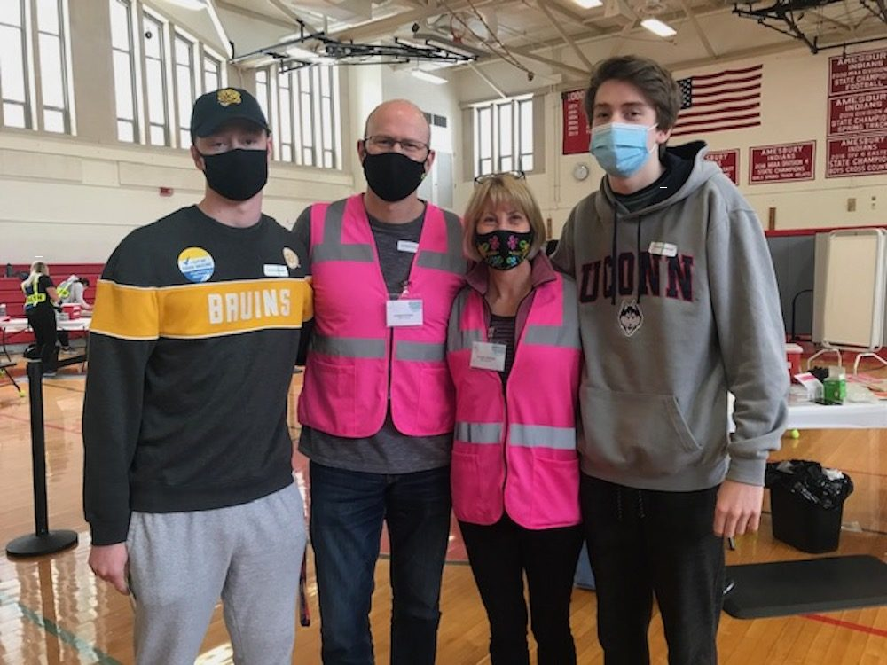 Jennifer Freeman, center right, son Matt, husband Doug and son Andrew at the Lower Merrimack Valley regional vaccine clinic, where the elder Freemans both volunteer. The teens were able to get vaccinated over the weekend.   COURTESY JENNIFER FREEMAN