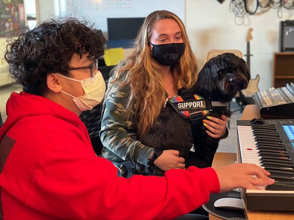 Stephen Phan and Carly Baker sit by the piano with service dog, Franklin, at North Shore Recovery High in Beverly. (Courtesy Mary Devin/North Shore Recovery High School)