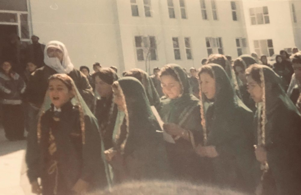Zarifa Hamidi, center with white paper, in the early 2000s at an orphanage in Afghanistan. (Courtesy)