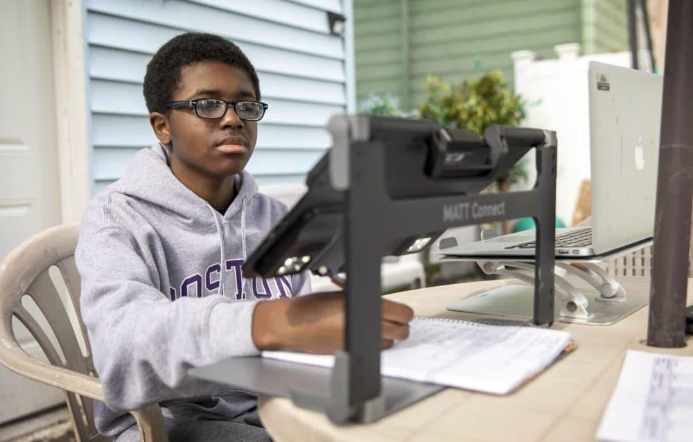 Michael Besson works on his homework in his backyard. (Robin Lubbock/WBUR)