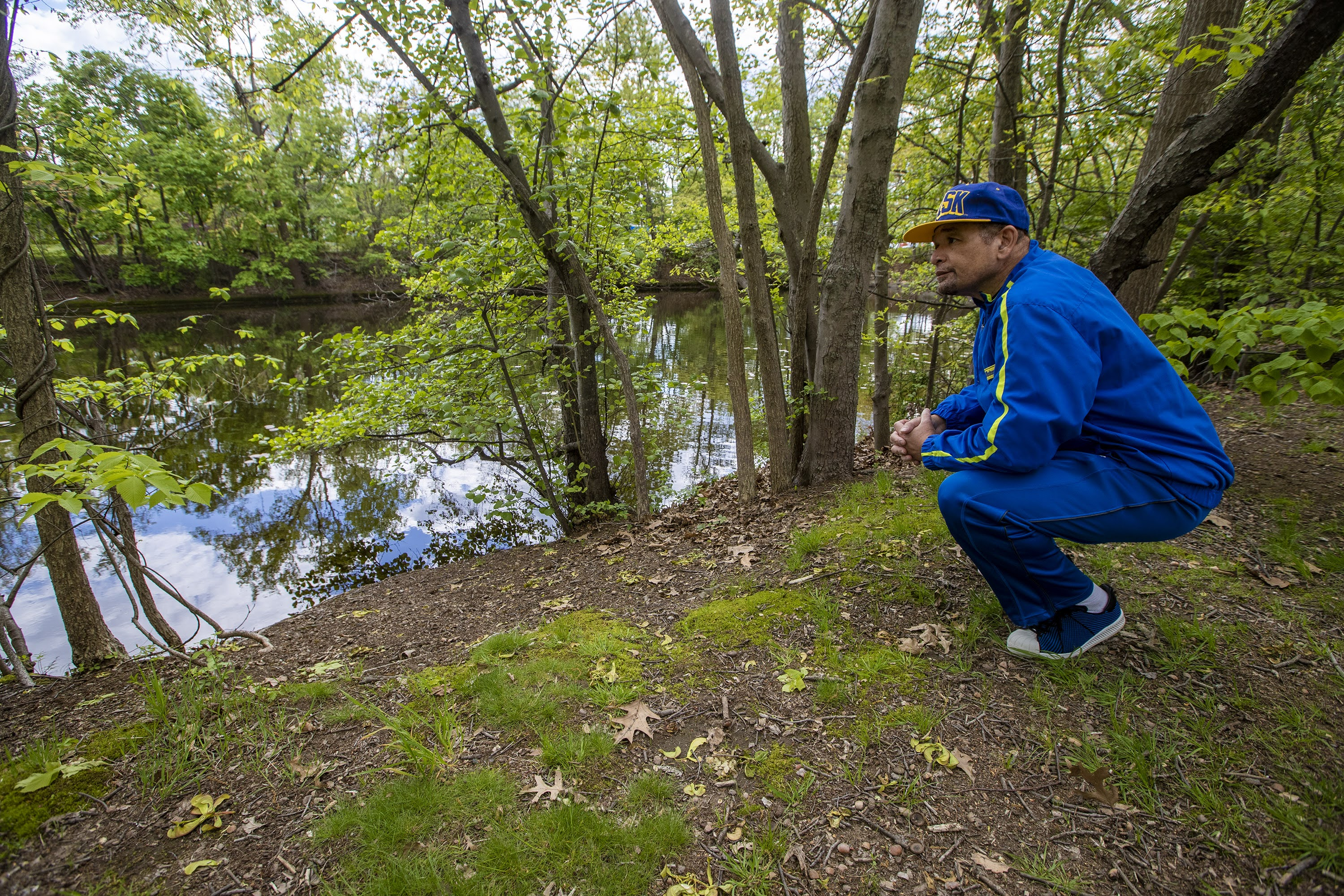 Poet Terry Carter kneels down to gaze at the Mystic River, along the banks in West Medford where he grew up. (Jesse Costa/WBUR)
