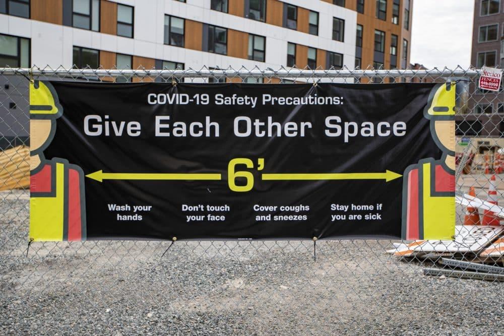 A COVID-19 safety precaution sign at a construction site in Central Square in Cambridge. (Jesse Costa/WBUR)