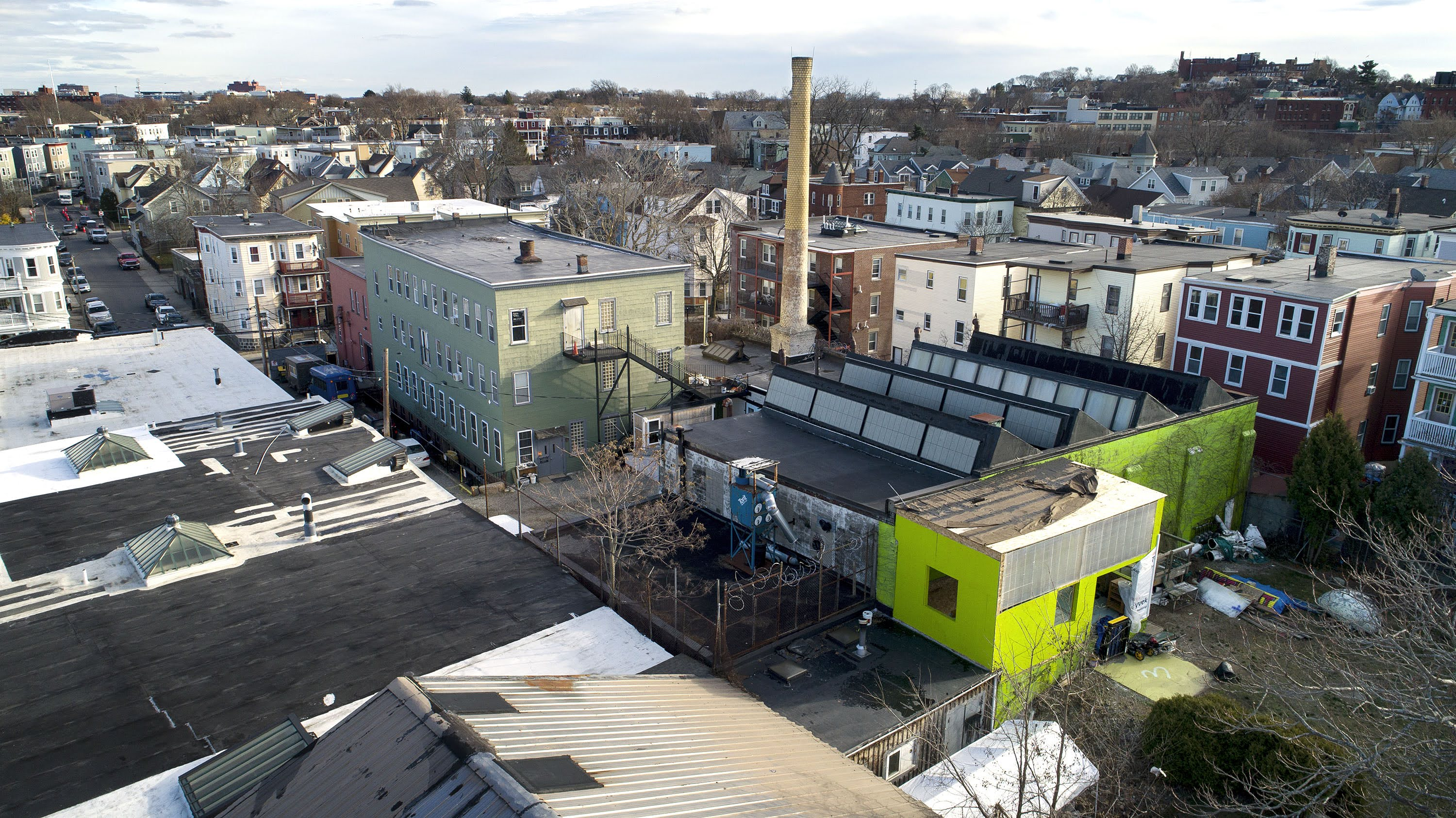 Humphreys Street Studios, with their landmark chimney and mostly green painted buildings, which were once a laundry facility in Dorchester, Mass. (Robin Lubbock/WBUR)