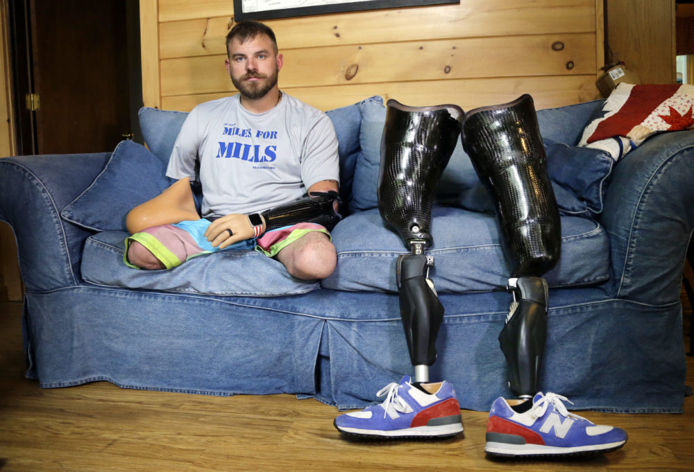 Travis Mills poses for a photo on his couch in Manchester, Maine. (Elise Amendola/AP)
