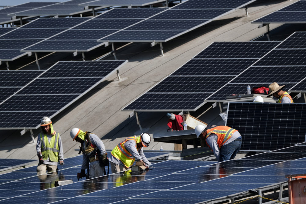 Workers install solar panels onto a roof in Los Angeles. (Richard Vogel/AP)