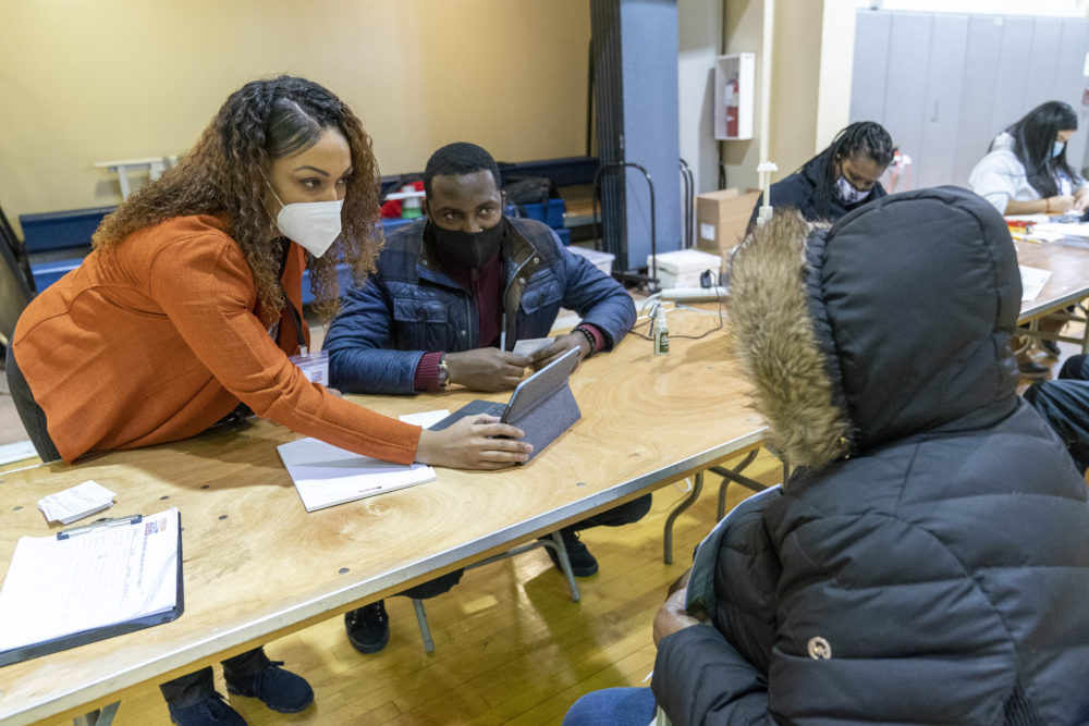 Crismely Tinidad, left, the Housing Service Coordinator at the Bronx River Community Center, translates for a resident who only speaks Spanish as he registers with a Somos Community Care screener at a pop-up COVID-19 vaccination site at the Bronx River Addition NYCHA complex, Sunday, Jan. 31, 2021. (AP Photo/Mary Altaffer)