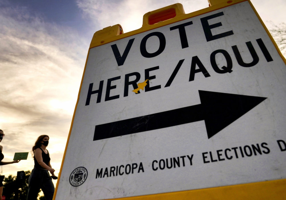 Voters deliver their ballot to a polling station in Tempe, Ariz., on Nov. 3, 2020, (Matt York/AP)