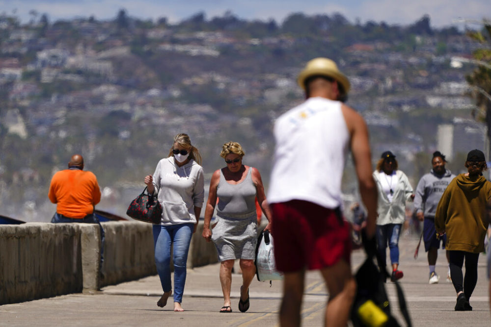 Jean Bourbonnais, left, wears a mask as she walks with Sheryl Nieman Hancock along a beach promenade Tuesday, April 27, 2021, in San Diego. Nieman Hancock is already vaccinated, and Bourbonnais plans to get her vaccine soon. U.S. health officials say fully vaccinated Americans don't need to wear masks outdoors anymore unless they are in a big crowd of strangers. And unvaccinated people can drop face coverings in some cases, too. (AP Photo/Gregory Bull)