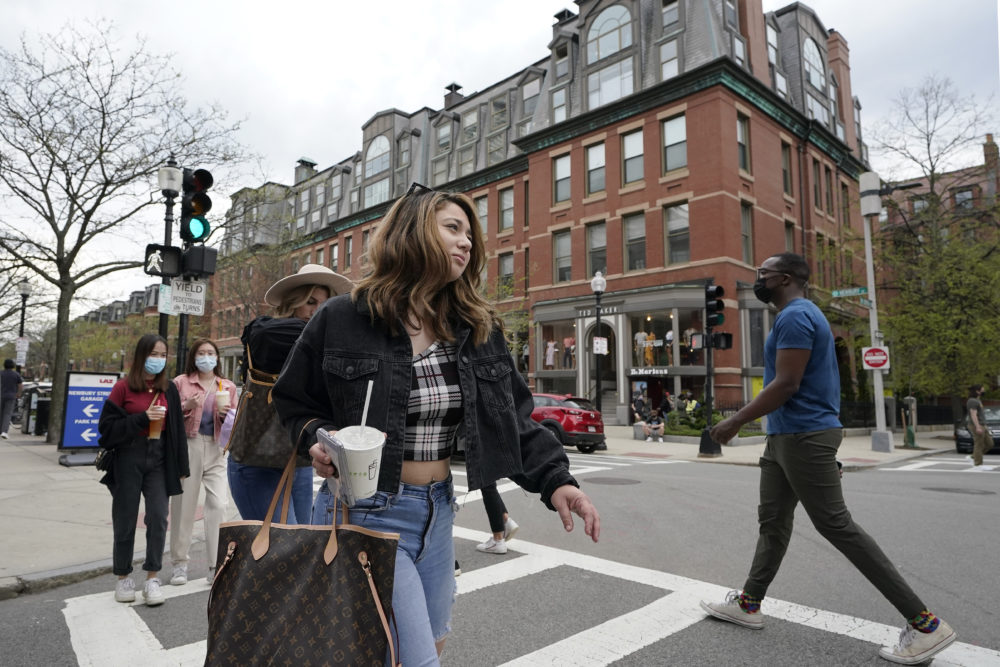 Pedestrians, some wearing masks out of concern for the coronavirus, while others go without masks, walk along Boston's fashionable Newbury Street, May 2, 2021.(Steven Senne/AP)
