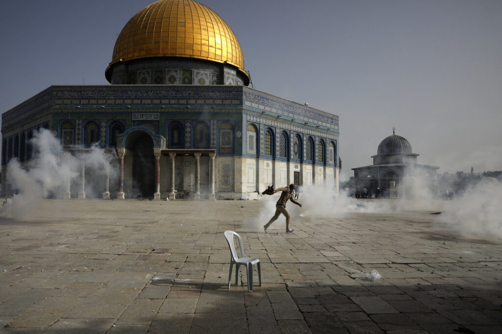 A Palestinian man runs away from tear gas during clashes with Israeli security forces in front of the Dome of the Rock Mosque at the Al Aqsa Mosque compound in Jerusalem's Old City Monday, May 10, 2021.  (Mahmoud Illean/AP)