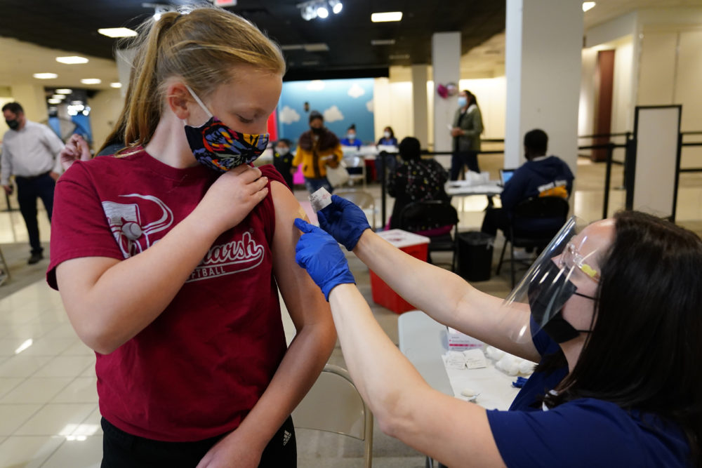 Olivia Edwards, left, 13, of Flourtown, Pa., gets a bandage from registered nurse Philene Moore after getting a Pfizer COVID-19 vaccination at a Montgomery County, Pa. Office of Public Health vaccination clinic at the King of Prussia Mall, Tuesday, May 11, 2021, in King of Prussia. (AP Photo/Matt Slocum)