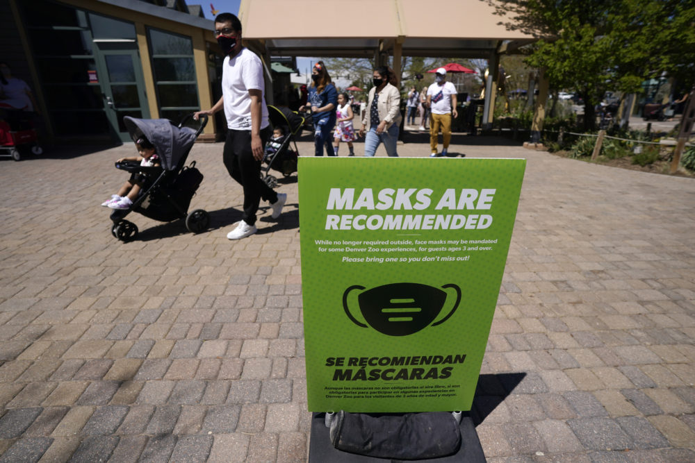 Although no longer required outside, a sign advises visitors to wear masks at the Denver Zoo in Denver on May 13, 2021. (David Zalubowski/AP)