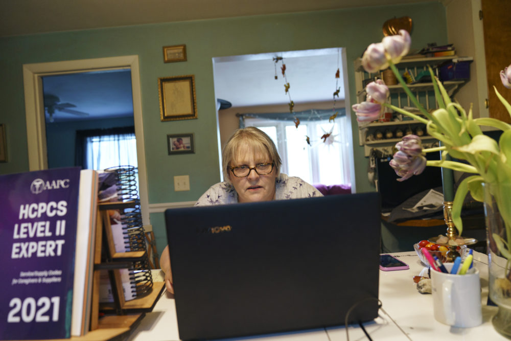 """Ellen Booth, 57, studies at her kitchen table to become a certified medical coder, in Coventry, R.I., May 17, 2021. When the restaurant she worked for closed last year, Booth said it gave her """"the kick I needed."""" She started a year-long class to learn to be a medical coder. (David Goldman/AP)"""