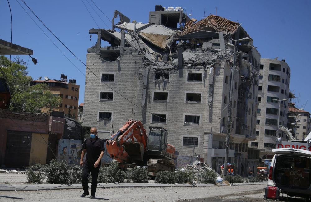A Palestinian walks by a building hit by an Israeli airstrike in Gaza City on Tuesday, May 18. (Hatem Moussa/AP)