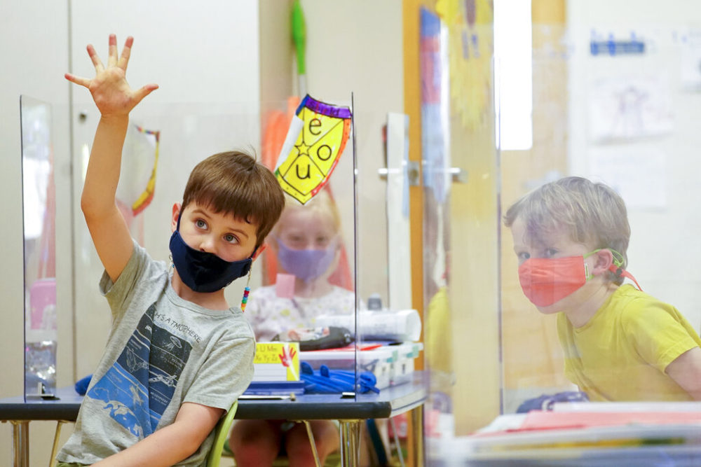 Kindergarten students wear their masks and are separated by plexiglass during a math lesson at the Milton Elementary School, on May 18, 2021, in Rye, N.Y. (Mary Altaffer/AP)