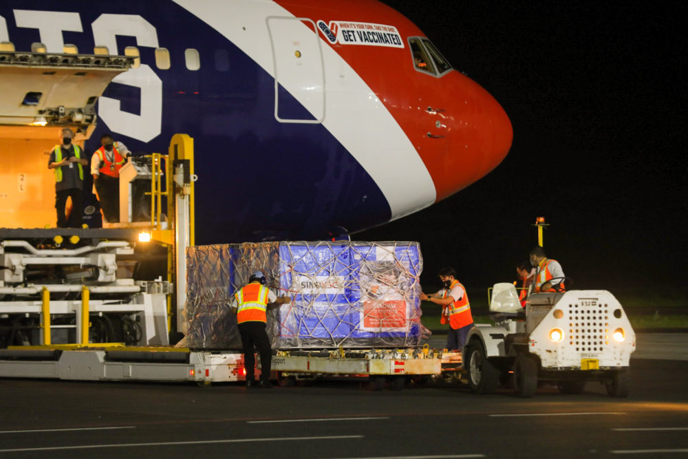 In this photo provided by El Salvador's presidential press office, airport workers unload a container of Chinese-made Sinovac COVID-19 vaccines from The New England Patriots team plane at the airport in San Salvador, El Salvador, Wednesday, May 19, 2021. (El Salvador's presidential press office via AP)