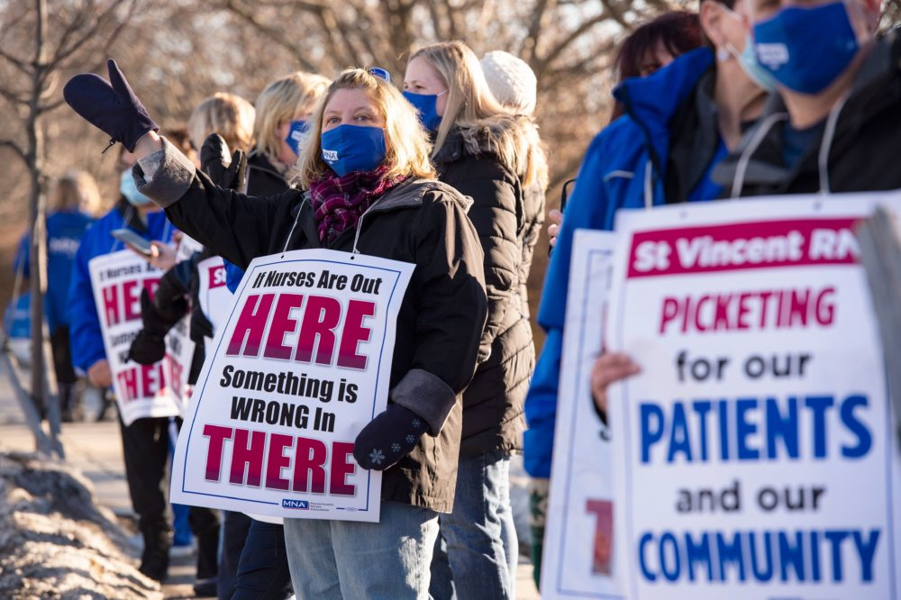 Registered Nurses and supporters stand in a picket line and wave to cars as they drive by outside St. Vincent Hospital in Worcester, Massachusetts on February 24, 2021. (Joseph Prezioso/AFP via Getty Images)