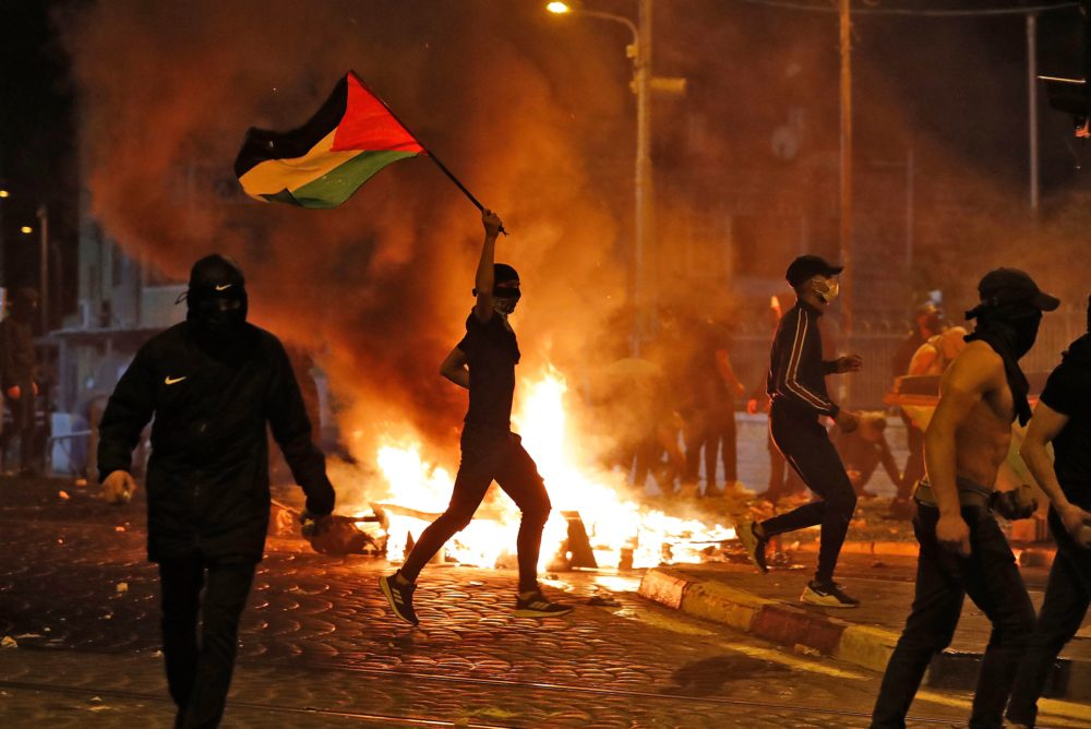 Palestinian protesters hurl stones during clashes with Israeli forces in the Shuafat Palestinian neighbourhood, neighbouring the Israeli settlement of Ramat Shlomo, in Israeli-annexed east Jerusalem on May 14, 2021. (Ahmad Gharabli/AFP via Getty Images)