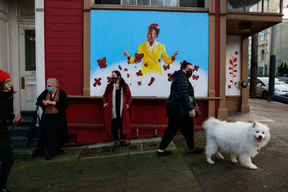 People pass by a mural of poet Amanda Gorman, painted by San Francisco muralist Nicole Hayden, center, on Page Street on Thursday, Jan. 28, 2021 in San Francisco, California. (Gabrielle Lurie/The San Francisco Chronicle via Getty Images)