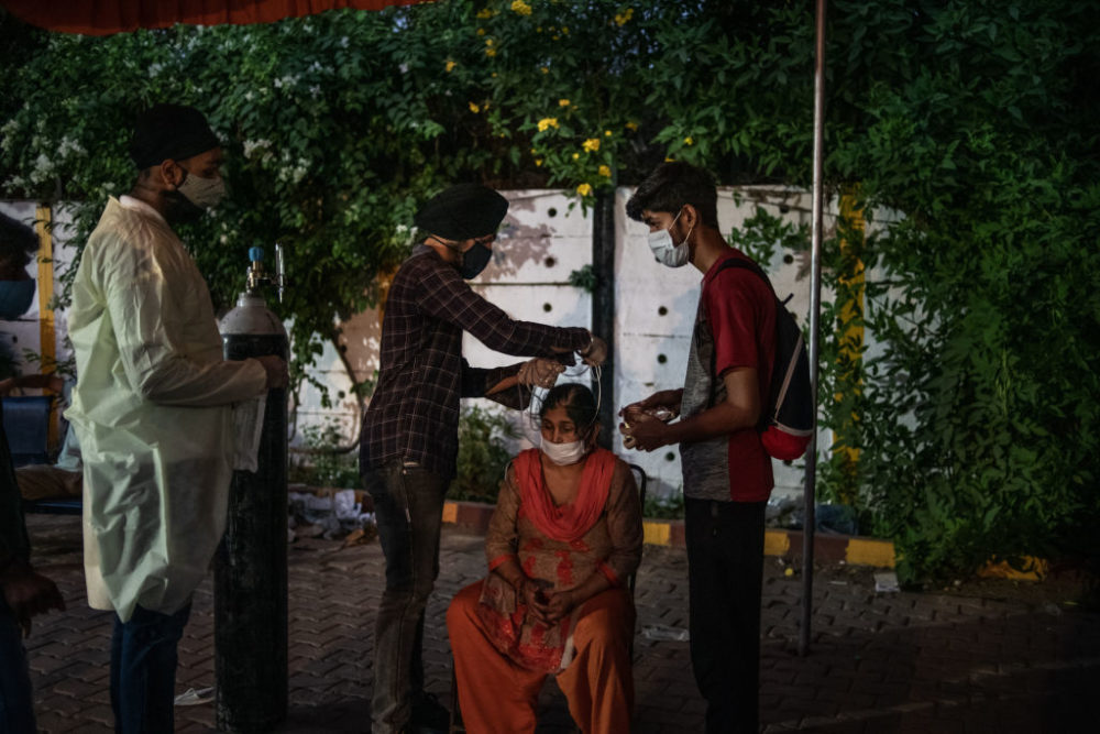 Volunteers treat patients suffering from Covid-19 with free oxygen at a makeshift clinic in a  parking lot outside the Gurdwara Damdama Sahib on May 03, 2021 in New Delhi, India. (Rebecca Conway/Getty Images)
