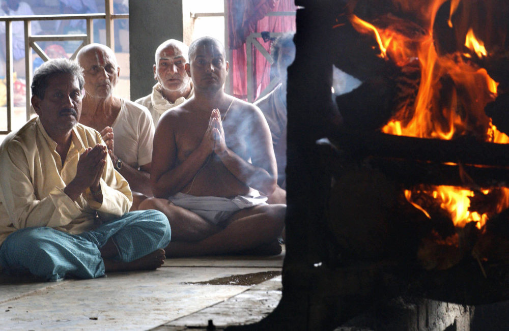Indian Hindu man Jeet Bahadur Singh (L) prays along with priests as he watches his wife's cremation at the Panchavati Amar Dham crematorium in Nashik, 28 August 2003 some 187 kms (116 miles) north of Bombay.  At least 45 people were killed and more than 70 injured in a 27 August stampede by Hindu worshippers rushing to bathe in one of western India's holiest rivers at the Kumbh festival held every three years.  AFP PHOTO/INDRANIL MUKHERJEE  (Photo credit should read INDRANIL MUKHERJEE/AFP via Getty Images)